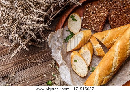 Homemade bread in wooden plate on table with wheat and linen cloth