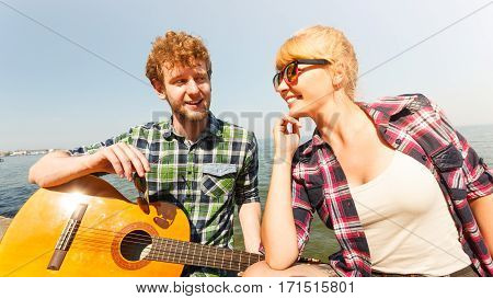 Young man hipster playing guitar for woman. Guy and girl in sunglasses relaxing on summer vacation.