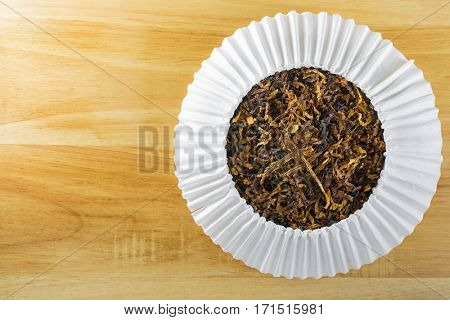 Closeup of classic blended aromatic pipe tobacco with vanilla flavor on bright wooden background with copyspace