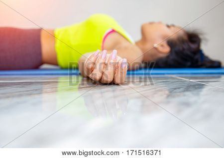 Young asian woman practicing in a yoga studio. Shavasana or corps pose is the end of a yoga class or practice.