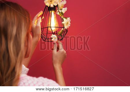 Woman decorating lamp with flower garland