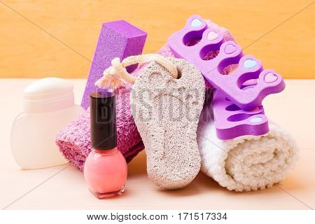 Foot care and cosmetics. Pedicure accessories set tools : pumice with footprint towel toe separators and pink varnish