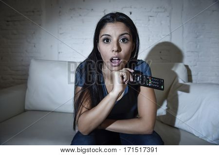 young latin woman at home sofa couch in living room watching television very concentrated and focused paying attention to tv news or program in disbelief face expression shocked and amazed