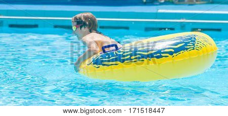 portrait of young boy having fun in water pool