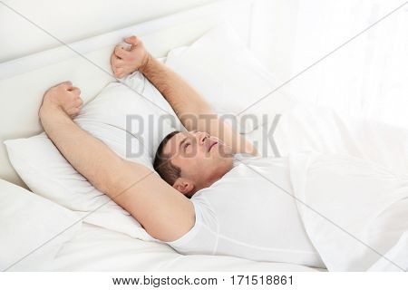 Young attractive man waking up in bed at home
