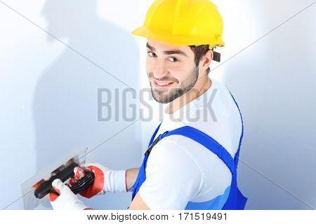 Young worker making repair in room