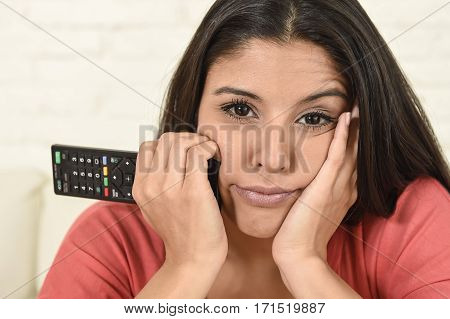 close up portrait of young beautiful hispanic woman sitting at home sofa couch in living room watching television looking tired and bored disappointed holding remote control in negative emotion