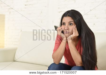 young beautiful spanish woman sitting at home sofa couch in living room watching television news looking tired and bored disappointed holding remote control in negative emotion