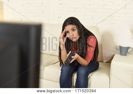 young beautiful hispanic woman sitting at home sofa couch in living room watching television news looking tired and bored disappointed holding remote control in negative emotion