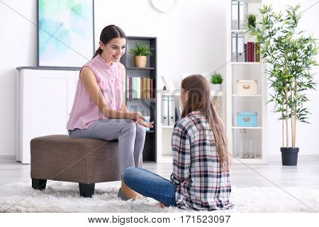 Young female psychologist working with teenager girl in office