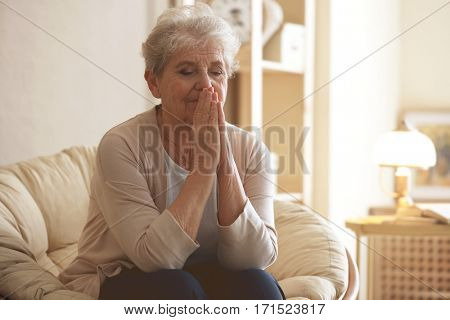Praying elderly woman sitting on lounge at home