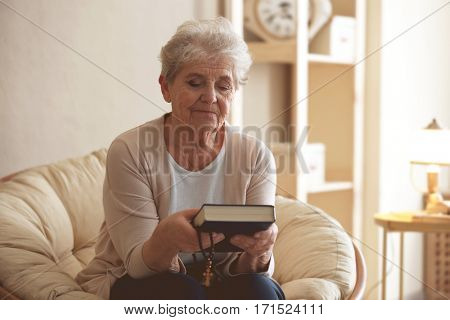 Elderly woman with Bible and rosary beads at home