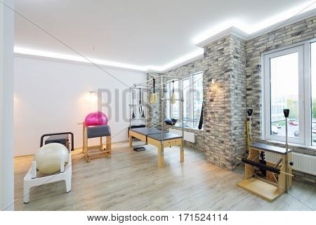 Hall with modern equipment for pilates training - fitballs and wooden trainers