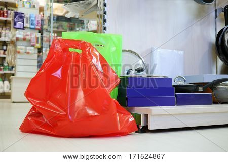 Red and green bags are on floor in supermarket Goods for Home with modern dishes