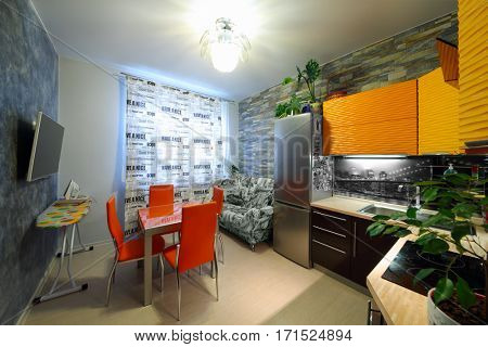 Empty stylish kitchen with couch, orange table and chairs in apartment