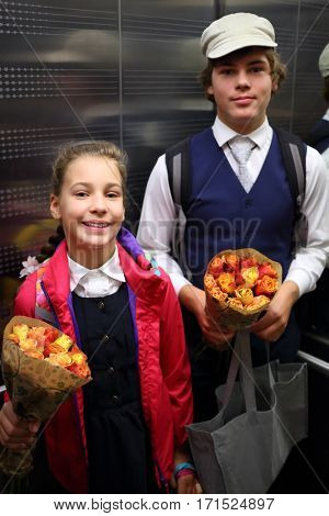 Happy boy and girl in school uniform with flowers are in elevator during September 1, focus on girl