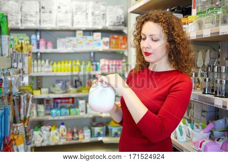 Pretty woman in red holds white teapot in Goods for Home shop