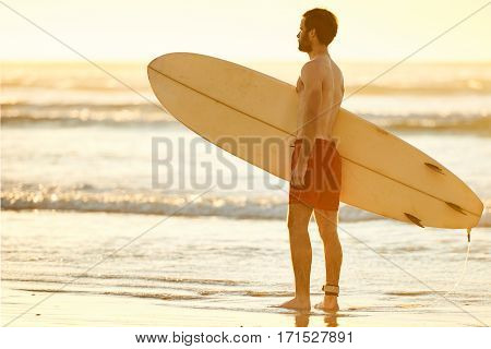 Young caucasian male wearing red shorts standing in the shallow waves on the beach while holding a surfboard perpendicular to himself.