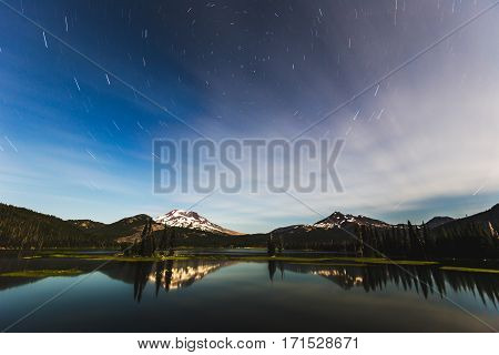 Long exposure of stars over beautiful mountains at Sparks Lake near Bend Oregon. Dark blue and black sky with stars over green forest and snowcapped mountains.