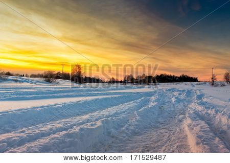 Snowmobile tracks on the ice of the river Pyhajoki in the Northern Finland. The setting winter sun casts beautiful light on the snow and creates dramatic shadows.