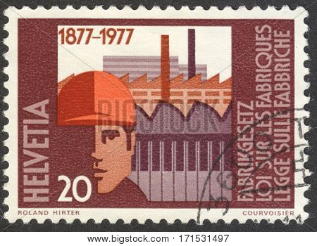 MOSCOW RUSSIA - CIRCA JANUARY 2017: a post stamp printed in SWITZERLAND shows Factory building & worker with safety helmet the series