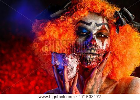 Close-up portrait of a terrible bloody clown with a mask. Halloween. Horror.