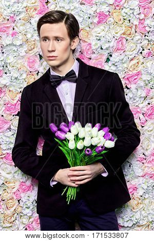 Handsome young man in an elegant suit with a bouquet of tulips over floral background. Valentine's Day, Women's Day, Mother's Day. Wedding concept.