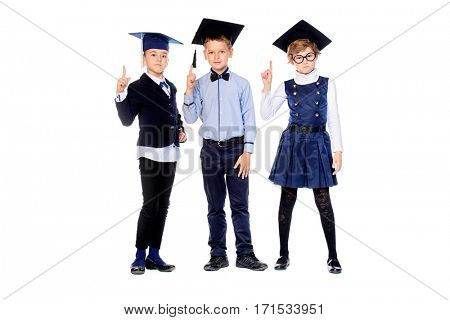 Full length portrait of three smart schoolchildren posing together in academic hats. School uniform. Education. Isolated over white.