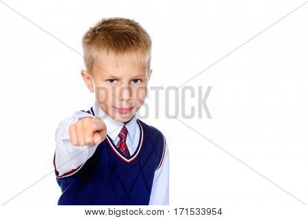 Serious schoolboy points his finger at the camera. Isolated over white background. Educational concept. Copy space.