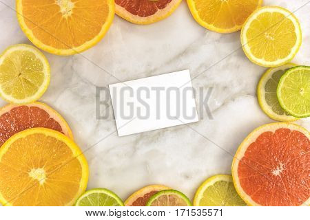 A vibrant frame made up of juicy citrus fruits, on a white marble texture, with a blank business card inside for copy space. Grapefruit, lime, lemon, and orange slices