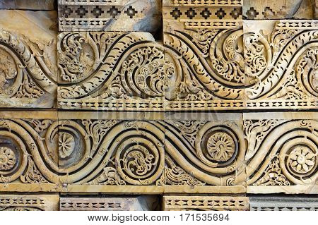 Indian bas-relief from stone with curly ornament in Qutub Minar