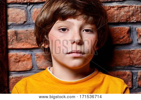 Portrait of a cute nine year old boy sitting on a floor leaning against the brick wall. Clothes for children. Kid's fashion.