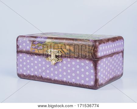 Picture of the closed purple-coloured box for bijouterie isolated on white background. Handmade decoupage jewel box. Side view.