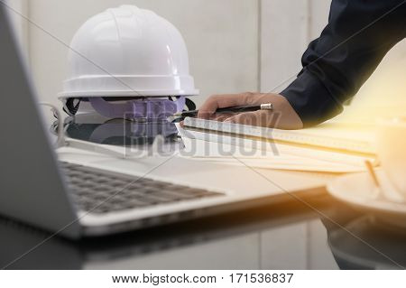 Image of engineer drawing plan on blue print in office near working site