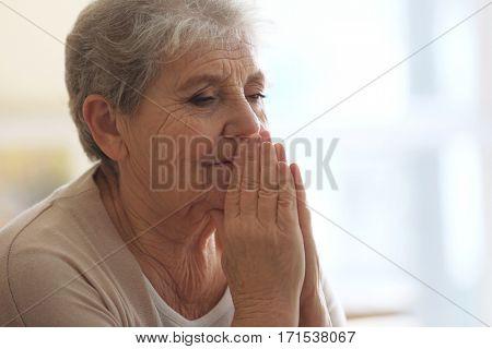Praying elderly woman at home