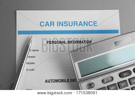 Car insurance form, calculator and pen on table