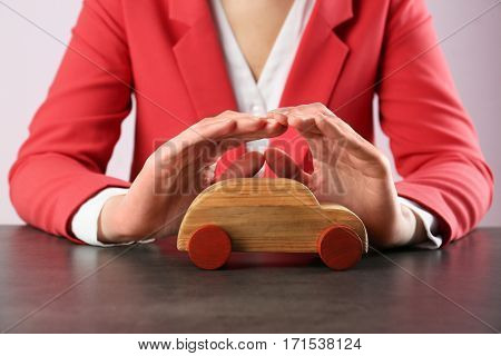 Car protection concept. Female hands and wooden toy car on table