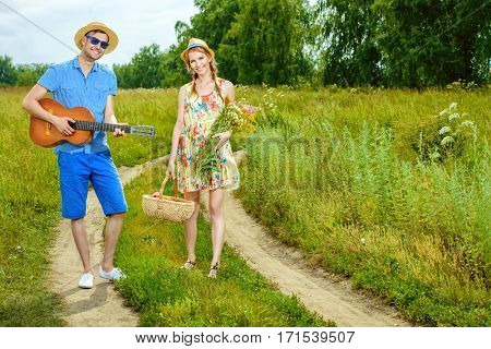 Enamored young man with a guitar singing his beloved girlfriend. They are walking along a country road on a sunny summer day. Love concept.