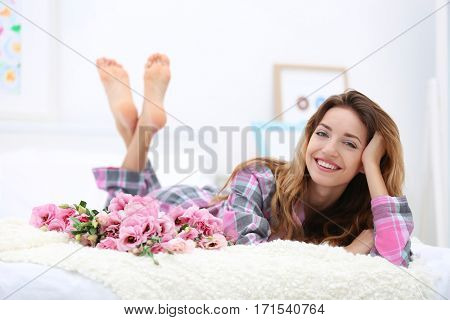 Young cheerful woman with beautiful bouquet of eustoma flowers lying on bed at home