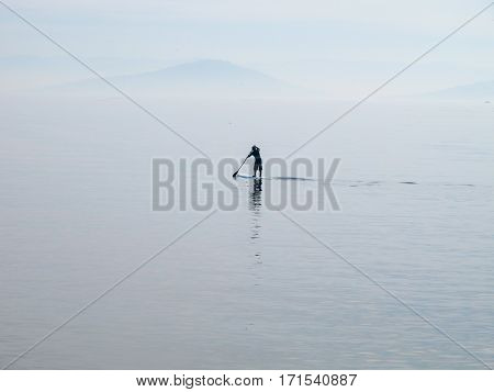 Lonely paddleboarder on the Marmara sea rowing  to isle.