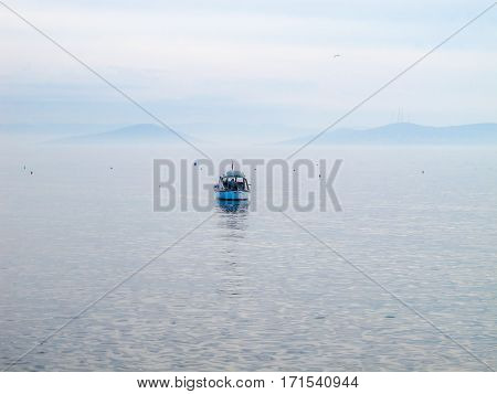 A single boat on The Marmara Sea. Islands in The Marmara Sea are visible at the background.