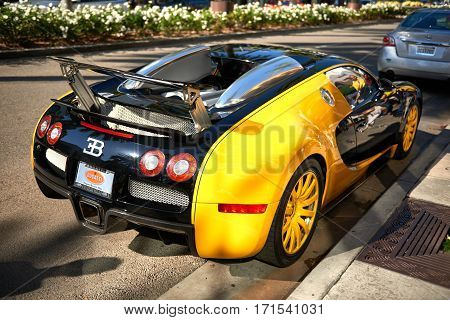 Yellow Bugatti Veyron parked on Rodeo Drive of Beverly Hills by dealership to attract tourists on Nov 2016.
