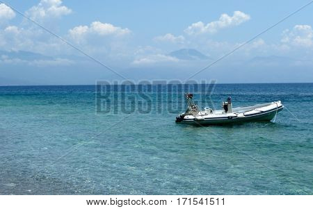 Inflatable boat anchored on the pebble beach