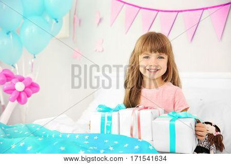Cute birthday girl sitting on bed with giftboxes