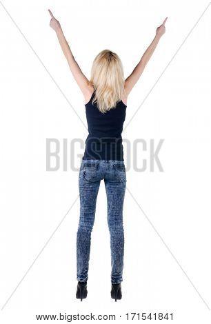 Beautiful young woman pointing at wall. Rear view.