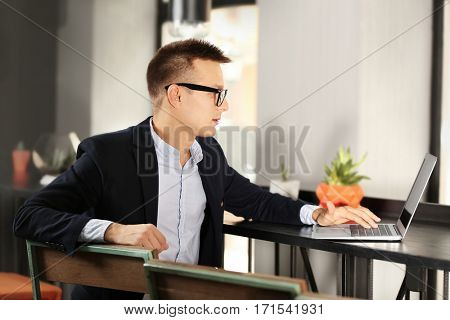 Handsome man with laptop studying in library