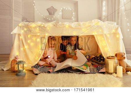 Cute little children reading book in hovel at home