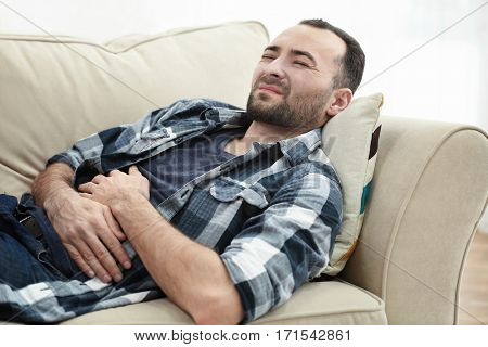 Handsome man suffering from stomach ache while lying on sofa at home