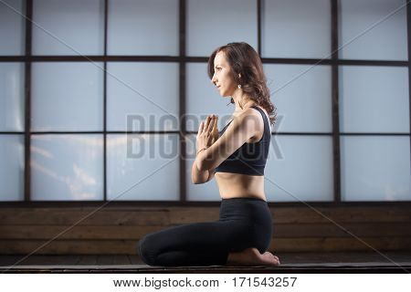Young attractive woman practicing yoga, sitting in vajrasana exercise, seiza pose with namaste, working out, wearing sportswear, black tank top, pants, indoor full length, studio evening practice