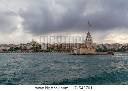 A view of maiden tower from ferry. Photo is taken in a cloudy day from ferry in Istanbul. City building in the background also visible.
